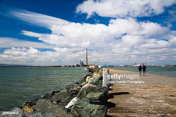 People walking along the Great South Wall towards the Poolbeg Chimneys in Dublin, Ireland