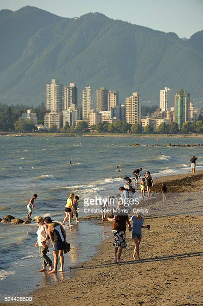 People walking along the shore at low tide at Kitsilano Beach on English Bay with a view of the skyline of downtown Vancouver and the Coast mountains