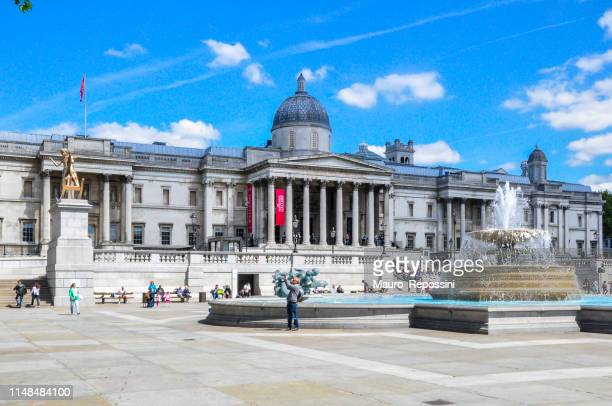 people walking and enjoying next to the national gallery and a water fountain during a sunny summer day in trafalgar square at london city, england, uk. - national gallery london stock pictures, royalty-free photos & images