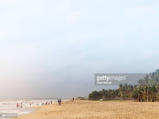People walking and playing in the evening light on Negombo beach