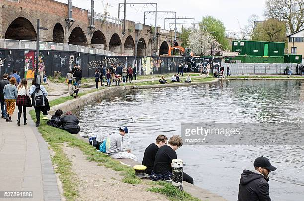 People walking and sitting along Paddington Basin during day Springtime