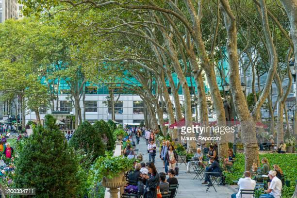 アメリカ合衆国ニューヨーク市マンハッタンのブライアントパークで、歩いたり、木の隣に座ったりしている人たち。 - ブライアント公園 ストックフォトと画像