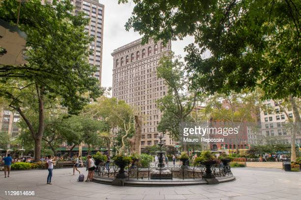 people walking and sitting on benches during summer in madison square park at midtown manhattan, new york city, usa - madison avenue stock pictures, royalty-free photos & images