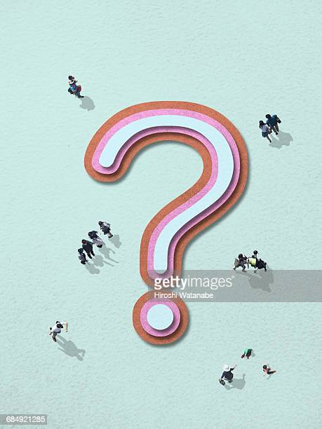 People walking around a question mark