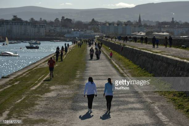 People walking at Dún Laoghaire West Pier, Dublin, on Sunday morning during Level 5 Covid-19 lockdown. On Sunday, 21 March in Dublin, Ireland.