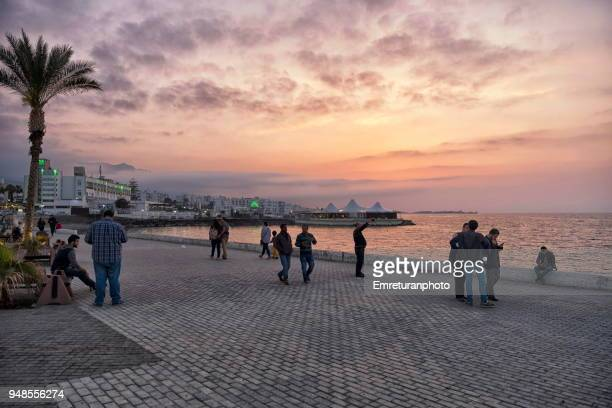 people walking at girne promenade at sunset. - emreturanphoto stock pictures, royalty-free photos & images