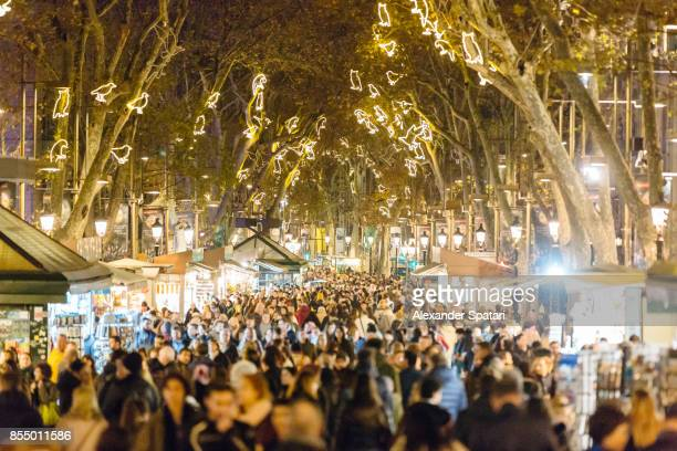 people walking at la rambla street during christmas and new year holidays in barcelona, catalonia, spain - feriado evento - fotografias e filmes do acervo