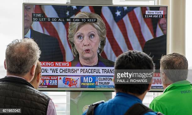 People walking at Ronald Reagan National Airport airport gather around a television monitor and watch US Democratic nominee Hillary Clinton deliver...