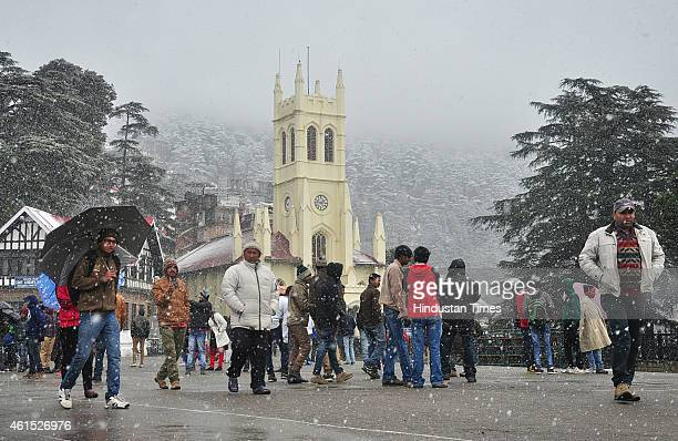 People walking at the ridge during snowfall in the backdrop of snow covered Jhaku hill on January 14 2015 in Shimla India Shimla and its surrounding...