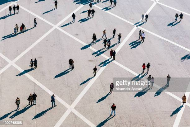 people walking at the town square on a sunny day - luchtfoto stockfoto's en -beelden