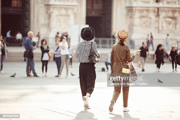 people walking at town square by duomo di milano - städtischer platz stock-fotos und bilder