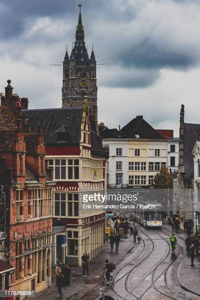 people walking by buildings in city against cloudy sky - belgium stock pictures, royalty-free photos & images