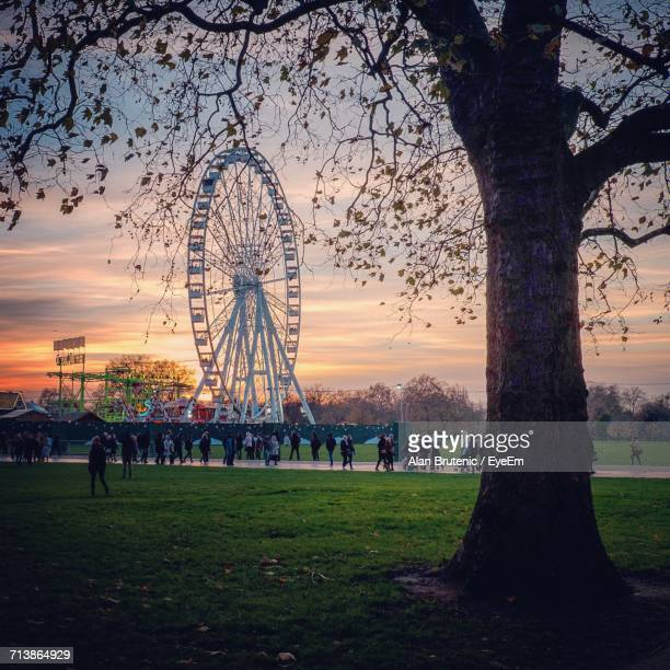 People Walking By Ferris Wheel At Park During Sunset