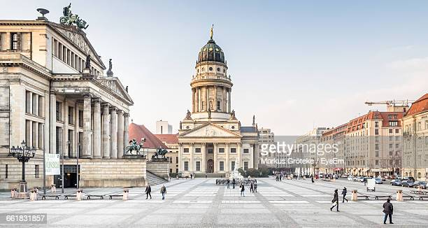 people walking by french cathedral at gendarmenmarkt - gendarmenmarkt stock pictures, royalty-free photos & images