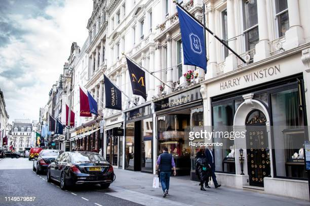 people walking by high end exclusive jewellery stores such as chanel, cartier in new bond, london, england - designer label stock pictures, royalty-free photos & images