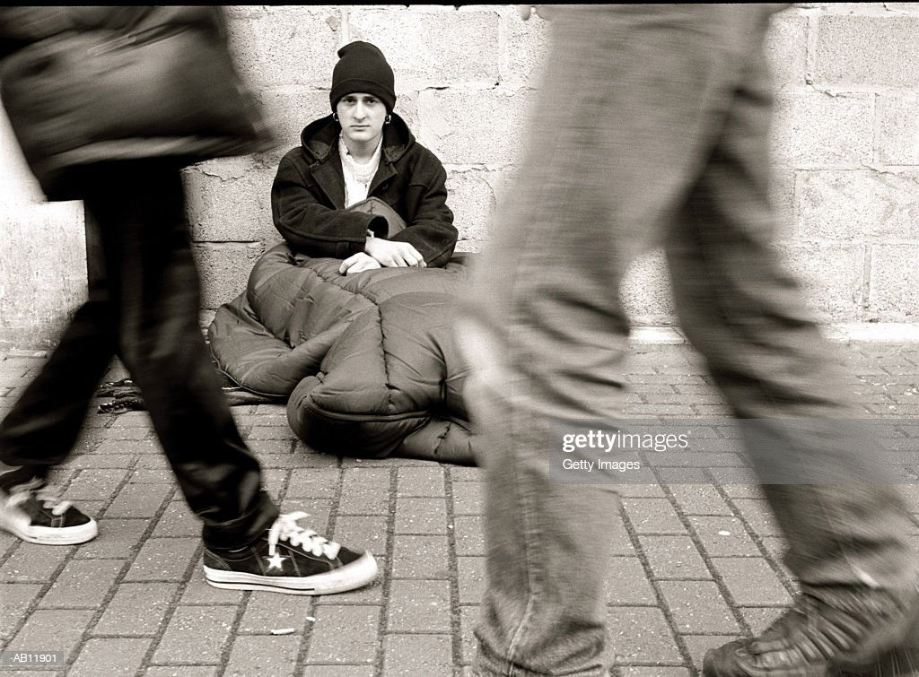 People walking by homless man, sitting on street, (B&W) : Stock Photo