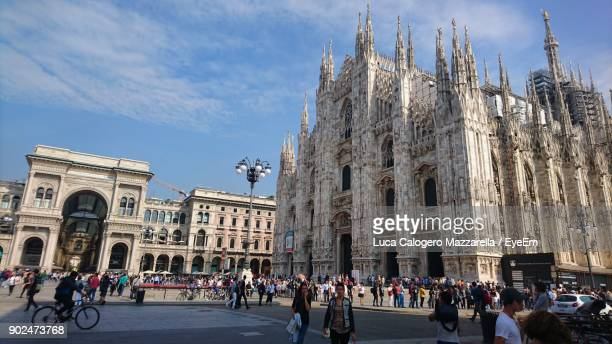 people walking by milan cathedral against sky in city - duomo di milano stock pictures, royalty-free photos & images