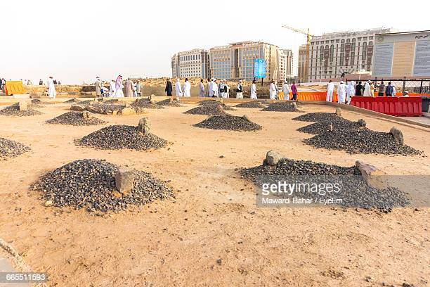 people walking by rocks on field at al-masjid an-nabawi - al madinah stock photos and pictures
