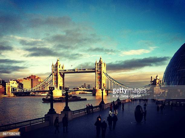 People Walking By Tower Bridge Over Thames River Against Sky
