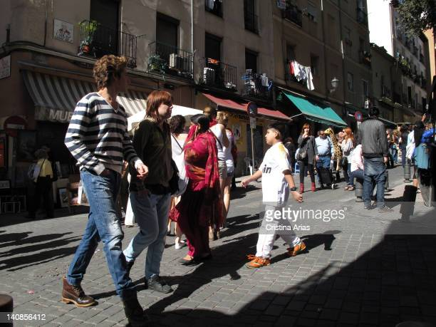 People walking down a street in El Rastro in Madrid the traditional outdoor market every Sunday morning Madrid Spain October 2011