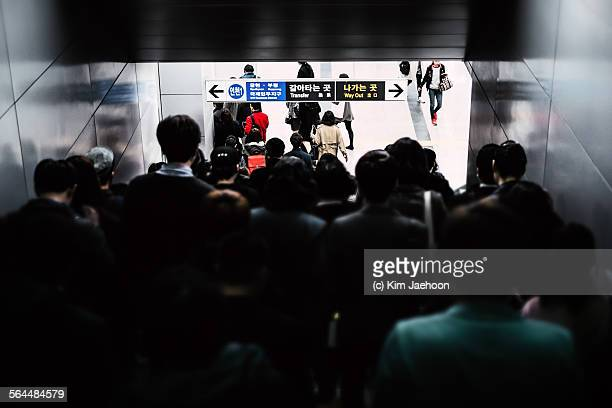 People walking down stairs in subway station.