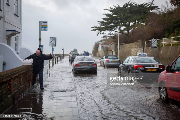 People walking down the A259 between Folkestone and Hythe which is flooded at Sandgate, Kent on the south coast of England, as Storm Ciara continues...