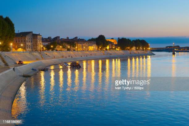 people walking embankment arles, france - quayside stock pictures, royalty-free photos & images