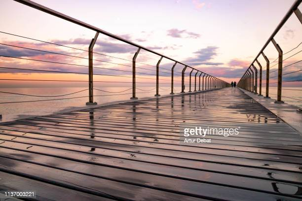people walking in a pier over the mediterranean sea during sunset. - maresme stock photos and pictures