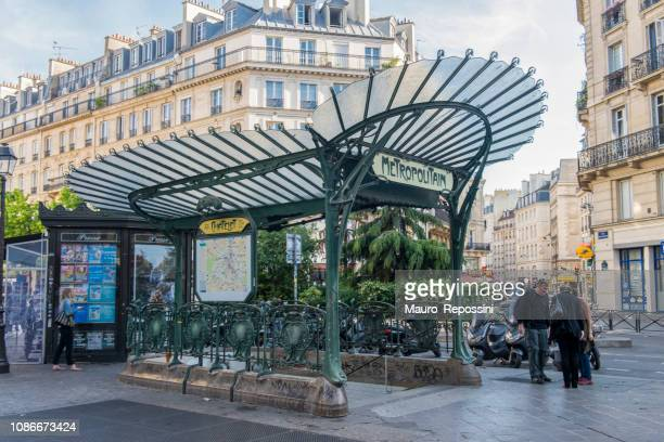 people walking in a small square next to an art nouveau entrance to a paris metro station at paris city, france. - art nouveau stock pictures, royalty-free photos & images