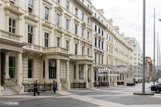 people walking in a street of kensington district next to three buildings at london, england, uk. - kensington and chelsea stock pictures, royalty-free photos & images