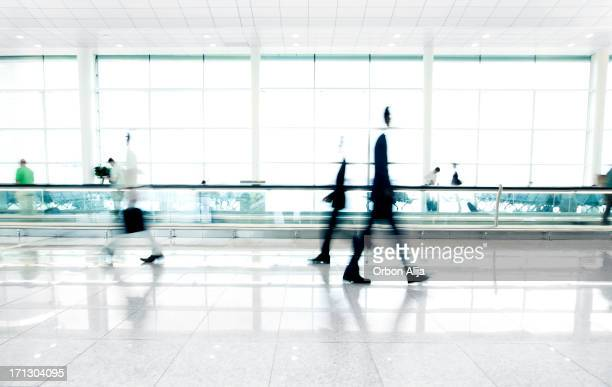 people walking in airport - pedestrian walkway stock pictures, royalty-free photos & images