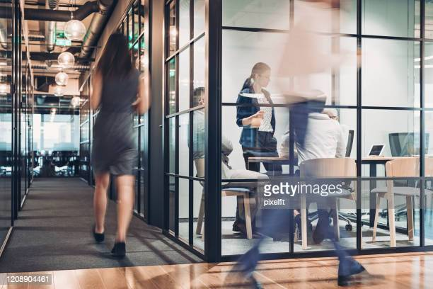 people walking in blurred motion in the office building - adults only stock pictures, royalty-free photos & images