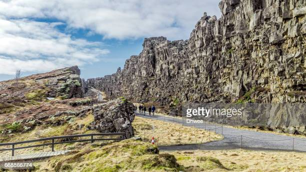 people walking in canyon of almannagja fault, thingvellir national park, iceland - pingvellir national park stock photos and pictures