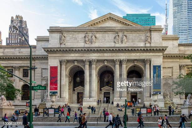 people walking in fifth avenue at the entrance of the new york public library in midtown manhattan, new york city, usa. - new york public library stock pictures, royalty-free photos & images
