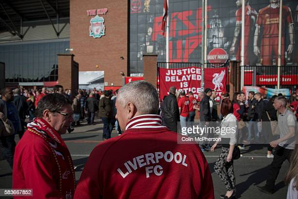 People walking in front of a banner commemorating the 1989 Hillsborough stadium disaster before the 25th anniversary memorial service to the disaster...