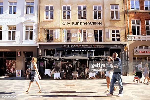 People walking in front of cafes in Kovenhagen .