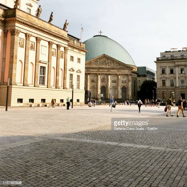 people walking in front of historical buildings in city - square composition stock pictures, royalty-free photos & images