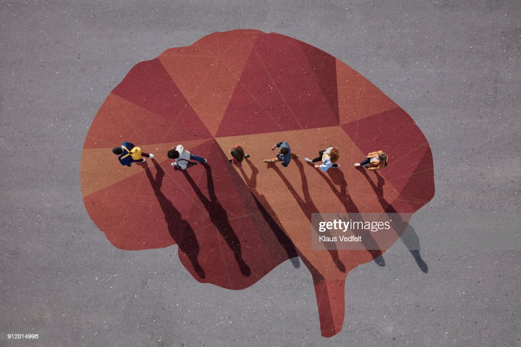 People walking in line across painted brain, on asphalt : Stock Photo
