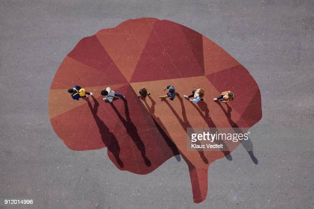 people walking in line across painted brain, on asphalt - 知能 ストックフォトと画像