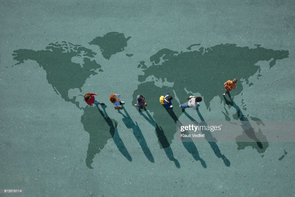 People walking in line across world map, painted on asphalt, front person walking left : ストックフォト