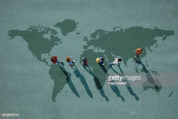 people walking in line across world map, painted on asphalt, front person walking left - globale kommunikation stock-fotos und bilder