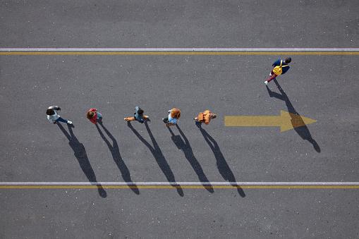 People walking in line on road, painted on asphalt, one person walking off. - gettyimageskorea