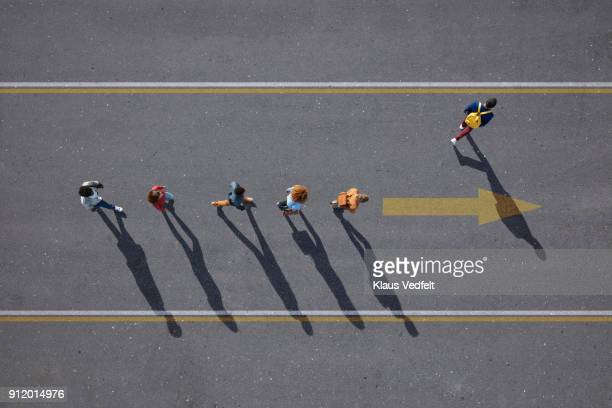 people walking in line on road, painted on asphalt, one person walking off. - verandering stockfoto's en -beelden