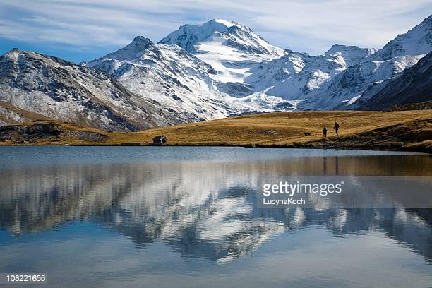 menschen gehen auf mountain valley und feld am see - lucyna koch stock-fotos und bilder