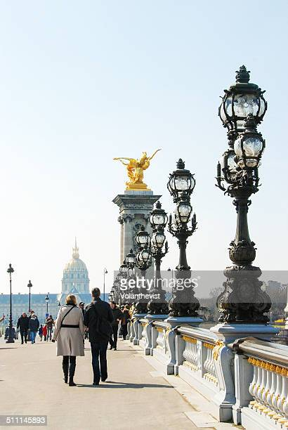 people walking in paris along a beautiful bridge - les invalides quarter stock photos and pictures