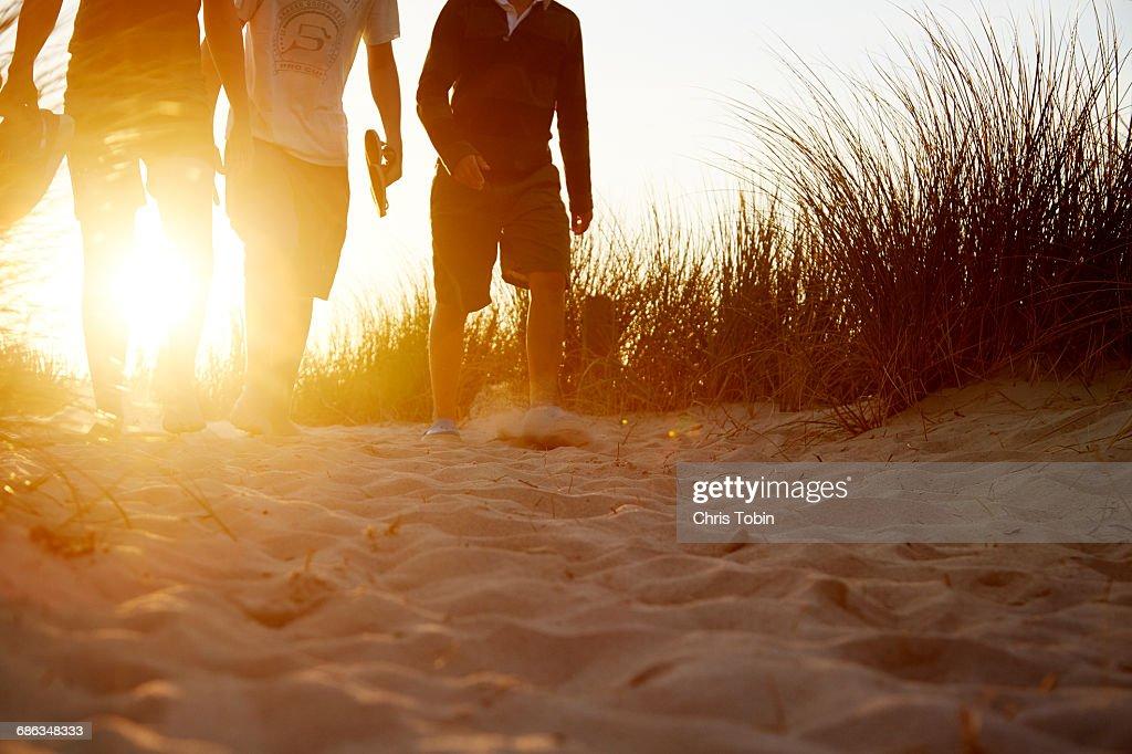 People walking in sandy dunes at sunset : Stock Photo