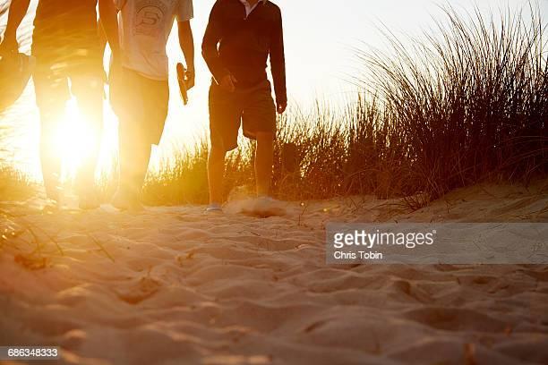 People walking in sandy dunes at sunset