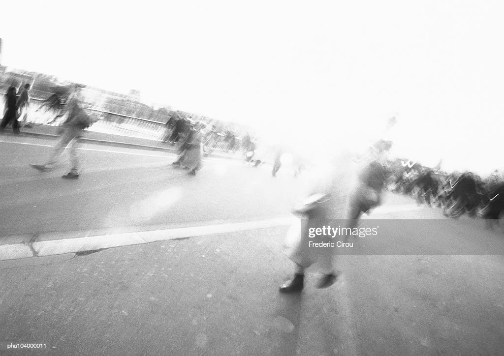 People walking in street, blurred, b&w : Stockfoto