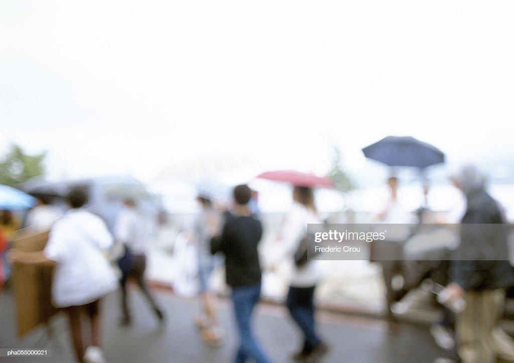 People walking in street with umbrellas, blurred : Stockfoto