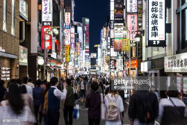 people walking in the crowded pedestrian streets of kabuki cho in shinjuku, in the heart of tokyo, japan capital city. - shinjuku bezirk stock-fotos und bilder